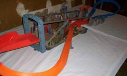 Cars race around track and jump over city. Cars propelled by battery operated thruster.