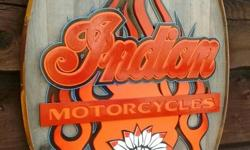 A one of a kind Indian Motorcycles Sign. The multi layered lettering, indian chief and flame graphics are all hand cut out using a scroll saw. The lettering and graphics are mounted to a nice weathered oval shaped cedar panel which is finished off with