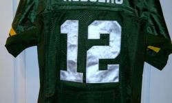 This is a youth large Aaron Rodgers Green Bay Packers Jersey. New with tags still on it. All names, numbers and logos are stitched on, not screened.