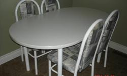 White oval table with 4 chairs.  Fabric has grey tones.