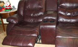 This is a wall hugger in burgundy with two seats and a divider between the seats with a compartment and two drink holders