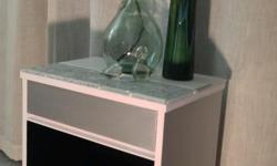 """Painted metallic silver, white and black with a glass and porcelain tiled top. Dimensions are 20"""" wide by 14"""" deep by 24"""" tall."""