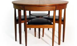 "This is a Hans Olsen for Frem Rojle, Danish 1950's teak dining table and set of four triangular chairs. The table has a circular top and turned tapered legs, 28 3/4"" (73cm) high, 42"" (106.7cm) diameter. The chairs with three legs, black vinyl covered"