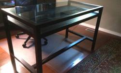 Tempered glass and wood-framed desk with pull-out drawer . Compartments to store and showcase items. Minimalist design is perfect for a clean, uncluttered look allowing natural light to pass through. Great for a small office setting. 30 inches high, 48