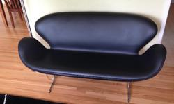 """Modern black leather sofa, with aluminum legs. Very good condition. Condo size, 57"""" overall width."""