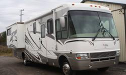 This is a 2005 National Dolphin LX 6342 powered by an 8.1L Vortec 8100 engine with an automatic transmission on a Workhorse chassis. This coach features a bedroom and living area slide-outs, power leveling, central air conditioning, furnace, window