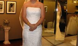 """This wedding dress was purchased here at Viva Bridal Boutique in Kamloops. Only been worn once. It is strapless and fairly fitted, beginning to flare at the knee into the train. Similar to a """"Mermaid style"""" dress. It laces up the back with the modesty"""
