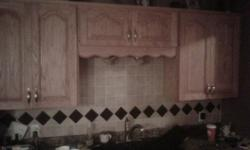 Solid Oak upper and lower kitchen cabinets for sale with fridge surround, wine holder and side cabinets. Includes polished brass handles.