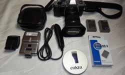 Contains: one Olympus EM-5 Body, one Olympus 12-50mm zoom lens. One Olympus Fl-300r Flash (never used), another smaller Olympus flash, 3 Olympus batteries, all straps, cables, software, one Remote cord, UV and CPol filters, David Busch Handbook for