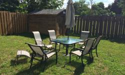 Used Patio Table set in good condition. Rust on chair arms. Table, 6 chairs, 2 foot stools and 1 mini table.