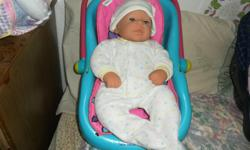 I'm Kimberly and I'm selling a sweet plush cuddly unisex baby doll with doll carrier included for only five dollars together. The doll is in good shape and is part of my collection. The baby doll has a cushy body and rubber arms and legs and is movable