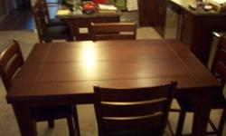 """Dark finish pub style dining room set with buffet, only 1 year old. Table includes 6 chairs with black leather seats. Includes jack-knife leaf.  Measurements without the leaf are 36"""" by 54"""" and 54"""" by 54"""" with the leaf. Buffet is 5 feet long and includes"""