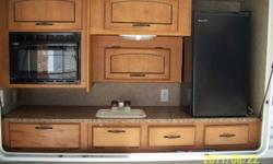 2011 30KDBSS Puma travel trailer. Super slide - sofa and u-shaped dinette .   L Kitchen, front queen bed with 3 bunks in rear. Front pass through storage, outdoor kitchen, outdoor shower, awning.  Two microwaves and two fridges.  One inside the camper the