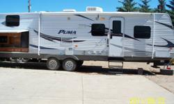 2011 Puma Travel Trailer 30 KDBSS.  Features include an outdoor kitchen with fridge, sink, microwave and campstove, outdoor shower, awing, hook-up for  a television, spare tire, air conditioning, furnance and much more.  Queen bed up front with pocket