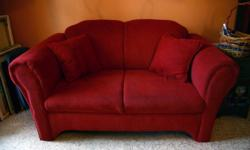 """Adorable dark red loveseat in great shape. It's about 5 years old and there's very slight wear on the front seating, but no rips or tears or scratches at all. Dimensions are 63"""" wide x 34"""" deep x 33"""" high. Comes with 2 reversable pillows. Smoke free"""