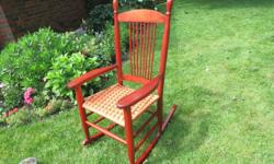 A very sturdy red rocking chair with a hand woven seat in excellent condition.