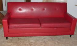 Red Vinyl Pullout Couch from the late 60?s to early 70?s. All original condition and great shape for the age. Canadian made, perfect for that retro apartment or vintage store. Also, the small blemish you see in the bottom right side of the photo is not in
