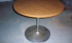 Table has a metal pedestal base and veneer top. Table top does have scratches as you can see by the pictures.