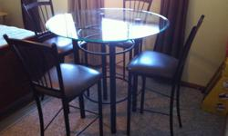Round Glass dining set with 6 chairs. 4 high chairs and 2 shorter chairs.