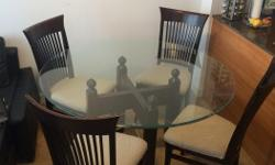 Glass dining table with solid wood base for sale with four wood chairs with upholstered seats. Set is in great condition with the exception of a few small nicks on the wood and small bleach spots on one of the chairs. Set comes with four chairs and large