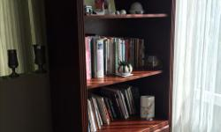 Lovely shelving unit in excellent condition. Has three shelves above with light and two shelves below behind solid doors. Solid wood in cherrywood color. Thanks, Monique