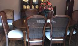 """This is solid cherry dining room set originally manufactured in Gibbard in Napanee, Ontario. It includes a buffet with an upper china cabinet, a table with 2 additional leaves, 2 captains chairs and 4 side chairs. The style is cald """"Chantilly"""" which is"""