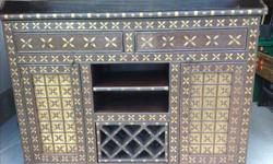 Beautiful solid Sheesham Cabinet brought back to Canada from India. Handmade with brass inlay, removable wine rack for extra storage. Two drawers and two cabinet doors with two inner shelves. Need to sell as it doesn't fit in our home. In Findlay Creek,