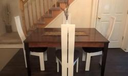 I have a stylish large 5 piece dining set for sale. In very good condition. Made of solid wood. The table has a combination of a dark legs with a lighter tone table. The set comes with 4 matching white chairs. The chairs have 2 different brown fabric. One