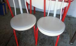 Table had 2 drop ends with red accents. 4 chairs are white vinyl with no tears and red accents.Set is in good condition.