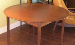 """Selling my 1960's teak dining table. Is stamped """"made in Denmark"""". It is round, 4' across, and oval when extended, 70"""" long. The leaf is built in. No nicks or scratches. $195.00 I will deliver to the GTA for $25.00 if needed."""