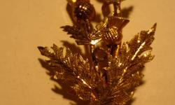 Gold Plated Thistle Style pin.1 3/4 inches long. Yellow amberish stones.Excellent condition. Vintage piece.