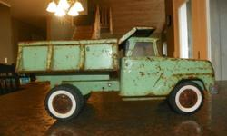 1965 Tonka Dump Truck No. 406 Fully operational Control levers for dumping and tailgate release. Tail gate adjust to 2 positions. Hub Caps have 5 triangle holes, white wall tires, smooth bumper, one piece grill with bumper with embossed Tonka, 2 large