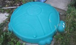 Green turtle sand box with play sand.