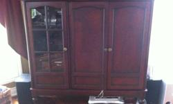 A beautiful cherry wood entertainment unit.  In immaculate condition. Dimensions 34'w x 55'h x 17'd