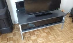 Grey and silver TV table with a smoked glass shelf which provides a lot of room for storing DVDs, etc. 38 inches long, 23.5 inches wide, 16.5 inches high $25. Thanks