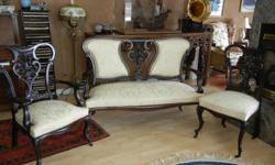 This beautiful three-piece Victorian mahogany parlour set features original horse hair and cabriole legs. The intricate detail of the dark walnut frame is emphasized against the new soft yellow upholstery. These three pieces have been cared for by a
