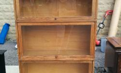 Solid wood 4 piece vintage bookcase. A beautiful well constructed piece of furniture. 3 separate bookcase stack on top of a base to form a tall bookcase or can be placed individually without the stand. Each bookcase has a glass cover which lifts open.