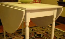 """White drop leaf table in pretty good condition. When table top is fully up it is 53"""" x 41"""". When table top is folded it is 22""""X41"""". It stands at 29"""" tall."""