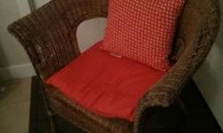 Selling a cute wicker patio chair with an orange cushion and pillow.