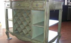 Free standing wine kitchen cabinet.  This Tuscan inspired unit is  made of solid wood.  The top is burnt umber  The sides are green with distressed edges. Each side is functional.  One one side is a wine rack with 3 drawers.  On the opposite side is a