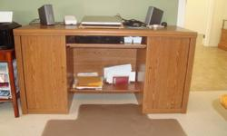 """Large 20 1/2"""" by 60"""" oak and veneer desk features a sliding keyboard drawer and spacious cupboards on either side with adjustable shelving. A great addition to a home office."""