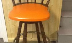 For sale 4 solid wood bar stools with upholstered seats. One chair has a small tear.